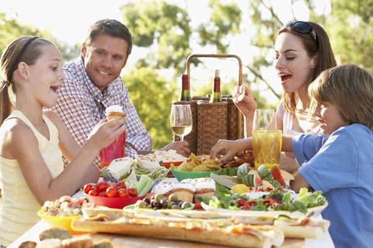 A Family enjoying a gift hamper at a picnic.